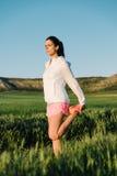 Frau, die bevor dem Laufen an der Landstraße ausdehnt Lizenzfreie Stockfotos
