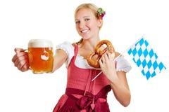 Frau, die Bier, Brezel und bayerische Flagge hält Stockfotos