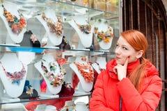 Frau, die bijouterie im Geschäftsfenster in Italien Murano wählt stockfoto
