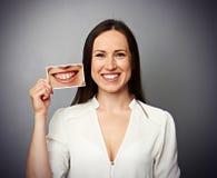 Frau, die Bild mit den gelben Zähnen hält Stockbild