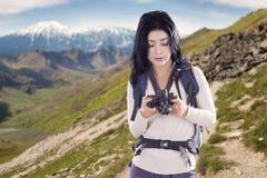 Frau, die Bilder von einer Digitalkamera schaut Stockfoto