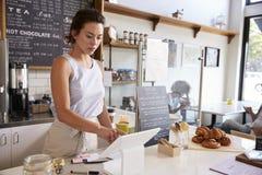 Frau, die an bis an einer Kaffeestube, Weitwinkel arbeitet Stockfotografie