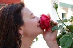 Frau, die bis zur Blume snuggling ist Lizenzfreie Stockfotografie