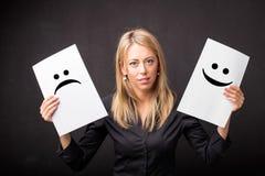 Frau, die Blätter mit den traurigen und glücklichen smiley hält Lizenzfreies Stockfoto