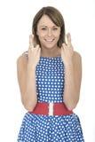 Frau, die blaue Polka Dot Dress Fingers Crossed trägt Lizenzfreie Stockfotos