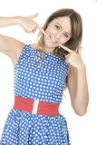 Frau, die blaue Polka Dot Dress Pointing an den Zähnen trägt Stockfoto