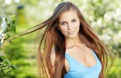 Frau, die blaues Kleid über Frühlingsobstgarten trägt stockfotografie