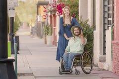 Frau, die blaues Kleid und Mann im Rollstuhl trägt Lizenzfreie Stockbilder