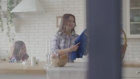 Frau, die blaues Schutzblech vom Korb nimmt und es wenigem M?dchen in der K?che gibt Vorbereitung f?r Ostern-Feiertag stock video