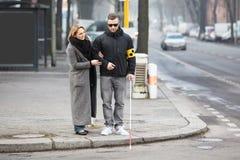 Frau, die Blinder auf Straße unterstützt Stockfotos