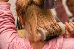 Frau, die blondes Haar mit Haartrockner und Rundbürste trocknet Stockbilder