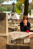Frau, die Blume auf Grab legt Stockfotografie