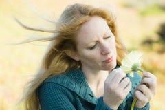 Frau, die Blume betrachtet stockbild