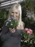 Frau, die zwischen Blumen wählt Stockbild
