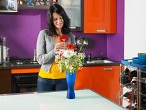 Frau, die Blumen im Potenziometer anordnet Lizenzfreies Stockbild