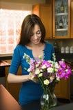 Frau, die Blumen in Vase einsetzt Lizenzfreie Stockbilder