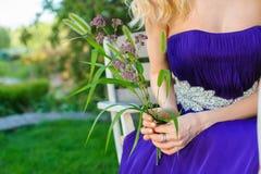 Frau, die Blumenstrauß von Wildflowers hält Stockfotografie