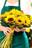 Frau, die Blumenstraußsonnenblumefloristen-Gelbblume anhält Lizenzfreie Stockfotos