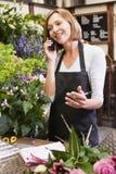 Frau, die am Blumensystem unter Verwendung des Telefons arbeitet Stockbild