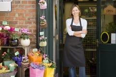 Frau, die am Blumensystemlächeln arbeitet Stockfoto