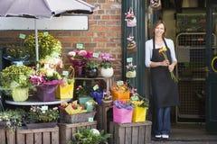Frau, die am Blumensystemlächeln arbeitet Stockbilder