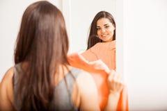 Frau, die Bluse vor einem Spiegel ausprobiert lizenzfreies stockbild