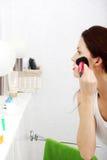 Frau, die Blusher in ihrem Badezimmer anwendet. lizenzfreies stockfoto