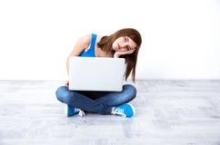Frau, die am Boden mit Laptop sitzt Lizenzfreies Stockfoto
