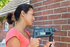 Frau, die Bohrmaschine auf Backsteinmauer hält stockfotografie