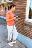 Frau, die Bohrmaschine auf Backsteinmauer hält lizenzfreie stockfotografie