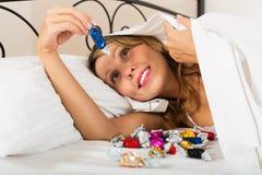 Frau, die Bonbons im Bett isst Lizenzfreie Stockfotos
