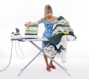 Frau, die an Bord vieler Kleidung bügelt Stockfoto