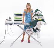 Frau, die an Bord vieler Kleidung bügelt Lizenzfreie Stockfotos