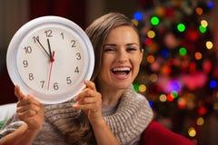 Frau, die Borduhr vor Weihnachtsbaum zeigt Lizenzfreies Stockfoto