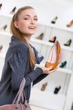 Frau, die braunes Leder auf den Fersen gefolgten Schuh hält Lizenzfreie Stockbilder