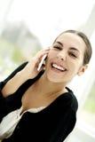 Frau, die breit lächelt, sprechend am Telefon Lizenzfreie Stockfotografie