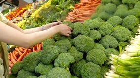 Frau, die Brokkoli im Gemischtwarenladen vorwählt stock video footage