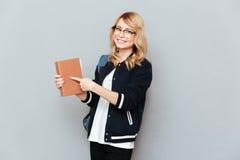 Frau, die am Buch darstellt Stockfotografie