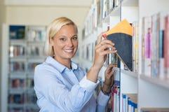 Frau, die Buch an der Bibliothek nimmt Lizenzfreies Stockfoto