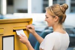 Frau, die Buchstaben in Briefkasten einfügt Lizenzfreies Stockfoto