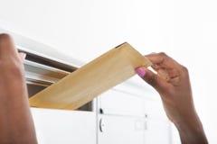 Frau, die Buchstaben in Briefkasten einsetzt Lizenzfreies Stockbild