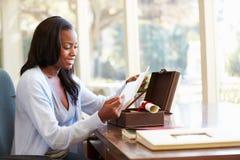 Frau, die Buchstaben im Andenken-Kasten auf Schreibtisch betrachtet Lizenzfreie Stockfotografie