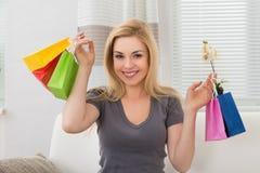 Frau, die bunte Einkaufenbeutel anhält Stockbilder
