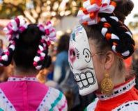 Frau, die bunte Schädelmasken- und -haarbänder für Dia de Los Muertos /Day der Toten trägt lizenzfreie stockbilder