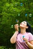 Frau, die bunte Seifenluftblasen durchbrennt Lizenzfreie Stockbilder