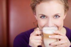 Frau, die Café Latte-Schale in der Kaffeestube hält Stockfotografie