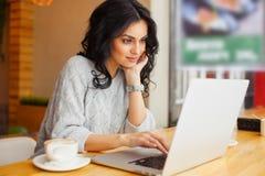 Frau, die am Café mit Laptop sitzt stockfoto