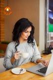 Frau, die am Café mit Laptop und Kaffee sitzt lizenzfreie stockfotos