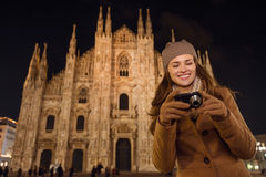 Frau, die in camera auf Fotos nahe Duomo am Abend, Mailand schaut Lizenzfreies Stockfoto