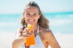 Frau, die in camera Flasche Sonnenblockcreme zeigt Lizenzfreie Stockbilder